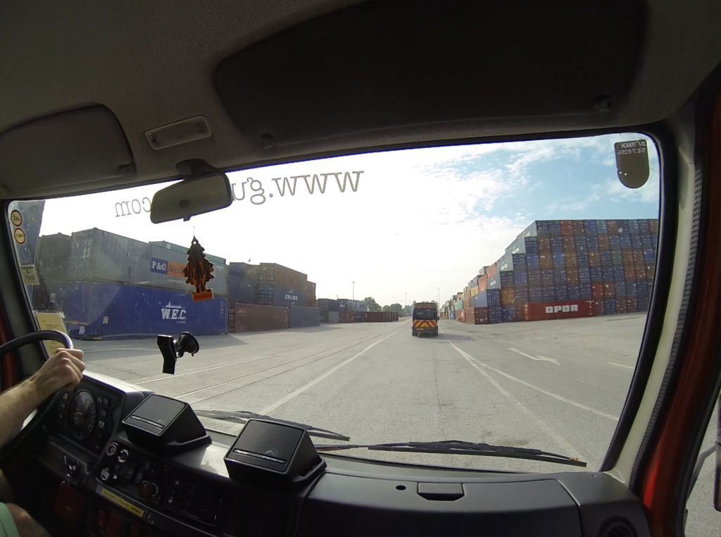 Following the escort vehicle through the port. Lots of containers...